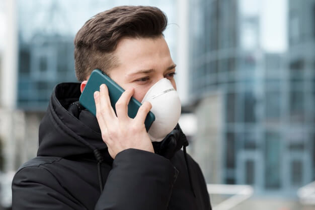 man talking phone while wearing medical mask